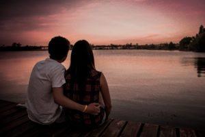Couple sitting close looking at a lake